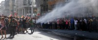 Turkish police use a water canon to disperse participants of a Gay Pride event in support of  Lesbian, Gay, Bisexual and Transsexual (LGBT) rights in Istanbul, Turkey, Sunday, June 28, 2015. Turkish police have used water cannons and tear gas to clear gay pride demonstrators from Istanbul's central square. Between 100 and 200 protestors were chased away from Taksim Square on Sunday after a police vehicle fired several jets of water to disperse the crowd. It wasn't immediately clear why the police intervened to push the peaceful if noisy protest away from the area.  (AP Photo/Emrah Gurel)