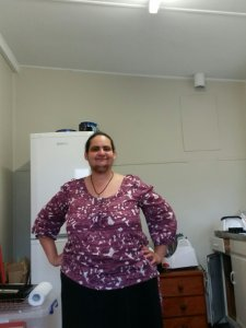 A profile picture of me, Karletta Abianac. I am standing, hands on my hips, smiling proudly, and wearing a nice woman's outfit. Long black skirt and purple and white patterned three quarter sleeved blouse. I have black facial hair which I intend to shave when I go out in a few days.