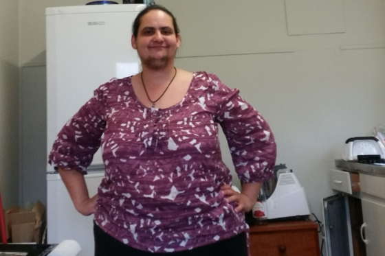 An overweight woman standing in a small, white kitchen, in front of a fridge. She is wearing a purple long sleeved shirt with white abstract patterns. Her hands are on her hips and she is standing and smiling. She has facial hair, longer than stubble on her lower face.